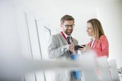 Gente di affari sorridente che utilizza Smart Phone nel centro di convenzione fotografia stock libera da diritti