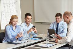 Gente di affari sorridente con gli aggeggi in ufficio Immagini Stock Libere da Diritti