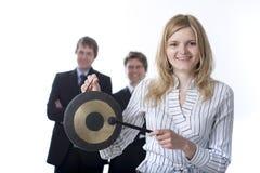 Gente di affari sorridente con un gong Immagini Stock Libere da Diritti