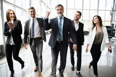 Gente di affari di Team Walking In Modern Office, uomini d'affari sicuri e donne di affari con il capo maturo In Foreground fotografie stock libere da diritti