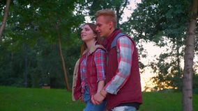 Gente di amore che cammina insieme nel parco di estate, circondato con la natura stupefacente e guardante avanti, fucilazione di  stock footage