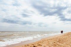 gente di camminata su una spiaggia vuota del mare immagine stock libera da diritti