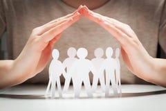 Gente di carta nell'ambito delle mani nel gesto di protezione Immagini Stock
