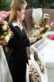 Gente di dolore al funerale con la bara immagine stock