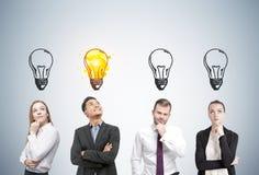 Gente di pensiero e lampadine, parete grigia Fotografia Stock Libera da Diritti