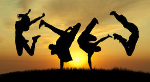 Gente di salto di felicità della siluetta sul tramonto fotografia stock libera da diritti