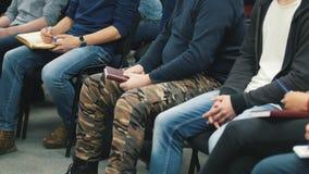 Gente differente - studenti o uomini d'affari ad una conferenza o ad una presentazione, officina, classe matrice - penne e taccui stock footage