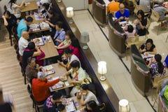 Gente dinning en un restaurante de los alimentos de preparación rápida Foto de archivo libre de regalías