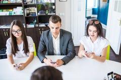 Gente diversa de la oficina que trabaja en los teléfonos móviles Empleados corporativos que sostienen smartphones en el encuentro fotos de archivo