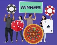 Gente diversa feliz que lleva a cabo iconos del casino imágenes de archivo libres de regalías