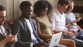 Gente diversa joven que usa los ordenadores portátiles y smartphones que se sientan en el sofá almacen de video