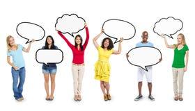 Gente diversa multiétnica que lleva a cabo burbujas en blanco del discurso Foto de archivo