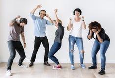 Gente diversa que baila junto escuchar la música imagenes de archivo