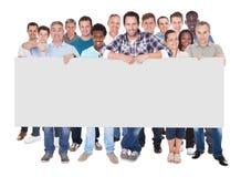 Gente diversa que lleva a cabo el cartel en blanco Fotografía de archivo libre de regalías