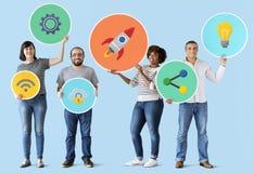Gente diversa que lleva a cabo iconos de la tecnología imagen de archivo