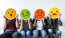 Gente diversa que lleva a cabo iconos del emoticon imagenes de archivo