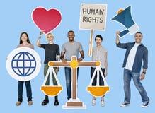 Gente diversa que lleva a cabo símbolos de los derechos humanos imagenes de archivo