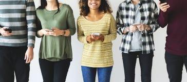 Gente diversa que se coloca con sus móviles a disposición fotografía de archivo libre de regalías