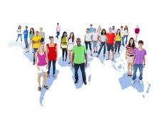 Gente diversa que se coloca en mapa del mundo Imágenes de archivo libres de regalías