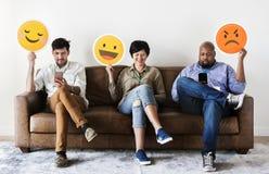 Gente diversa que sienta y que lleva a cabo logotipos de los emojis imagenes de archivo