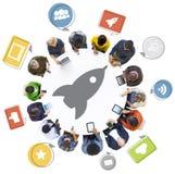 Gente diversa que usa los dispositivos con Rocket Symbol Imagen de archivo libre de regalías