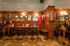 Gente divertida que bebe y que come dentro del café o de la barra retro elegante viejo con los espejos y los muebles de madera foto de archivo libre de regalías
