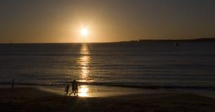 Gente durante puesta del sol   Imagen de archivo