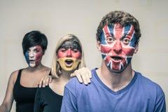 Gente emocionada con las banderas europeas en caras Imagen de archivo libre de regalías