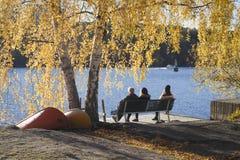 Gente en banco por el agua, enmarcada en colores hermosos del otoño Fotos de archivo libres de regalías