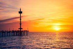 Gente en Brighton Jetty en la puesta del sol Foto de archivo