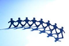 Gente en cadena con el corazón en medio Fotos de archivo