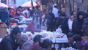 Gente en campo chino del mercado que compra o vende algo yunnan China foto de archivo