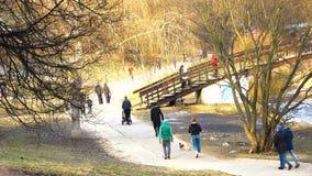 Gente en chaquetas y capas que camina en el parque en primavera temprana cerca del río con un puente redondeado almacen de metraje de vídeo