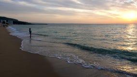 Gente en el admirind de la playa una salida del sol almacen de metraje de vídeo