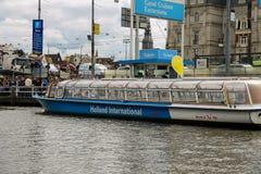 Gente en el aterrizaje en los barcos de cruceros del río, Amsterdam del muelle Foto de archivo libre de regalías