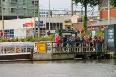 Gente en el aterrizaje en los barcos de cruceros del río, Amsterdam, red del muelle Foto de archivo libre de regalías