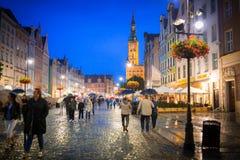 Gente en el carril largo de la ciudad vieja en Gdansk en la noche, Polonia Fotos de archivo