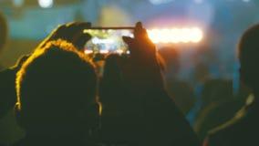 Gente en el concierto de rock de la música que toma las fotos o que registra el vídeo con smartphones almacen de video
