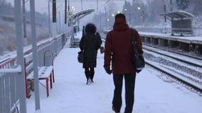 Gente en el ferrocarril que espera un tren suburbano, vídeo de la cámara lenta almacen de metraje de vídeo