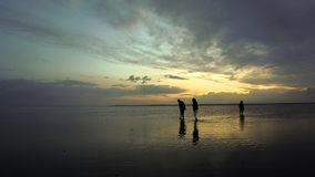 Gente en el lago de sal en la puesta del sol fotos de archivo libres de regalías