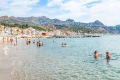 Gente en el mar cerca de la costa de Giardini Naxos Foto de archivo libre de regalías