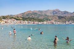 Gente en el mar jónico en la playa en Giardini Naxos Imagenes de archivo
