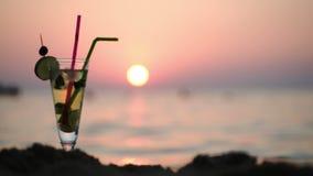Gente en el mar y cóctel en la playa en la puesta del sol almacen de metraje de vídeo