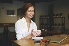 Gente en el ordenador portátil moderno del trabajo que reconstruye en el buen humor que se sienta en café Fotografía de archivo libre de regalías