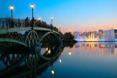 Gente en el puente y la fuente en puesta del sol. Moscú. Fotografía de archivo libre de regalías