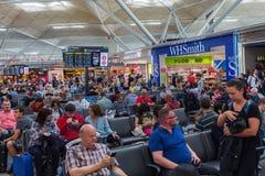 Gente en el salón de la salida del aeropuerto de Londres Standsted foto de archivo libre de regalías