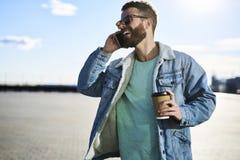 Gente en el trabajo durante la conversación telefónica mientras que bebe el café Foto de archivo libre de regalías