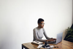 Gente en el trabajo mientras que usa Internet del ordenador portátil y de la radio interior Foto de archivo libre de regalías