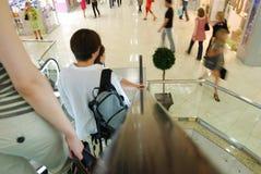 Gente en escaleras móviles Imágenes de archivo libres de regalías