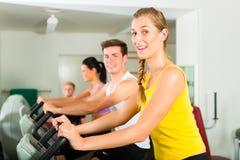Gente en gimnasio del deporte en la máquina de la aptitud Imagen de archivo